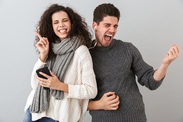 Portrait de couple ludique homme et femme écoutant de la musique avec des écouteurs et dansant, isolé sur mur gris