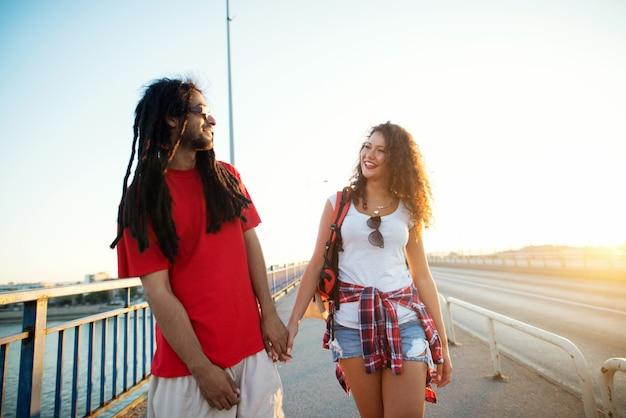 Portrait d'un couple main dans la main en marchant sur le pont.