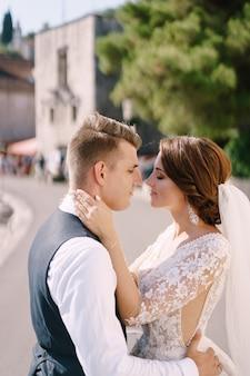 Portrait d'un couple de mariage dans la rue, la mariée embrasse le marié par le cou le marié la serre dans ses bras