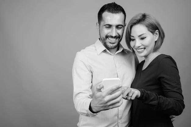 Portrait de couple multi ethnique ensemble et amoureux sur gris en noir et blanc