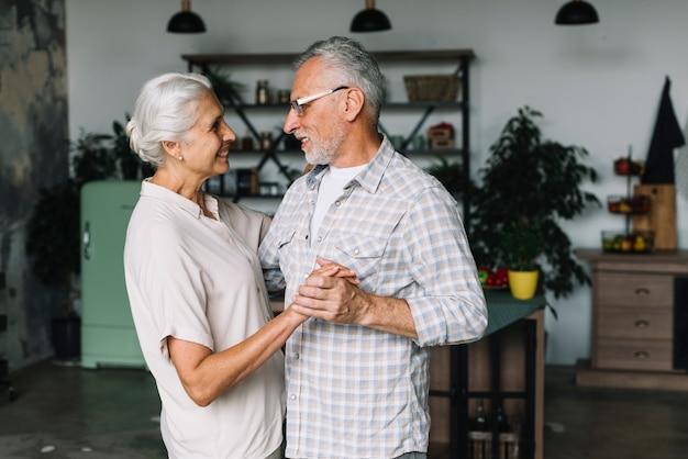 Portrait de couple de personnes âgées dansent ensemble dans la cuisine