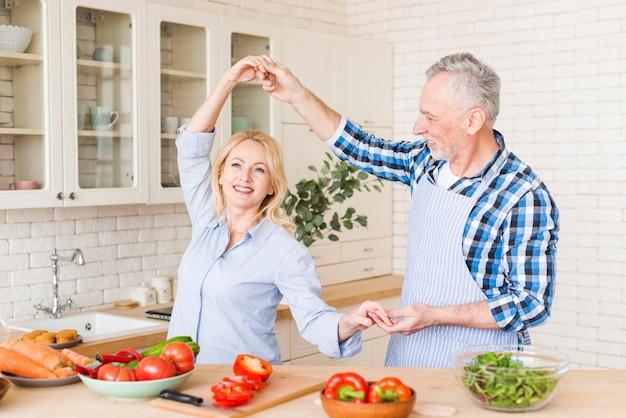 Portrait d'un couple de personnes âgées heureux danser dans la cuisine
