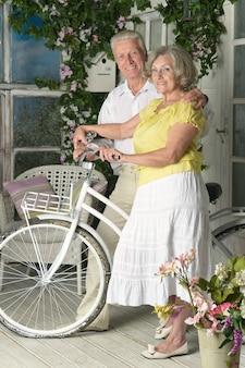 Portrait d'un couple de personnes âgées heureux avec vélo