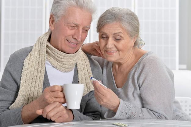 Portrait d'un couple de personnes âgées malades avec thermomètre