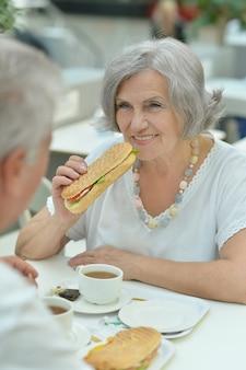 Portrait d'un couple de personnes âgées mangeant de la restauration rapide