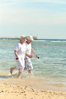 Portrait d'un couple de personnes âgées marchant sur la plage