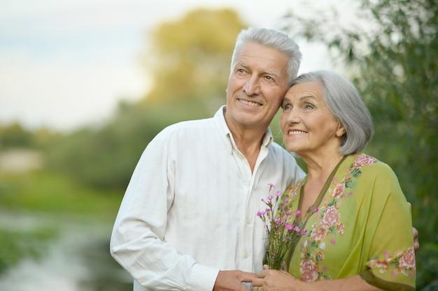 Portrait d'un couple de personnes âgées se reposant au parc d'été