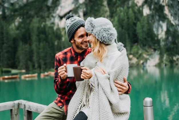 Portrait d'un couple romantique d'adultes visitant un lac alpin à braies italie en hiver