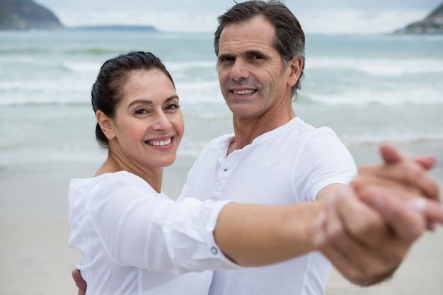 Portrait de couple romantique dansant sur la plage