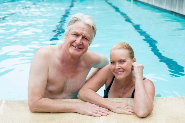 Portrait de couple se penchant au bord de la piscine