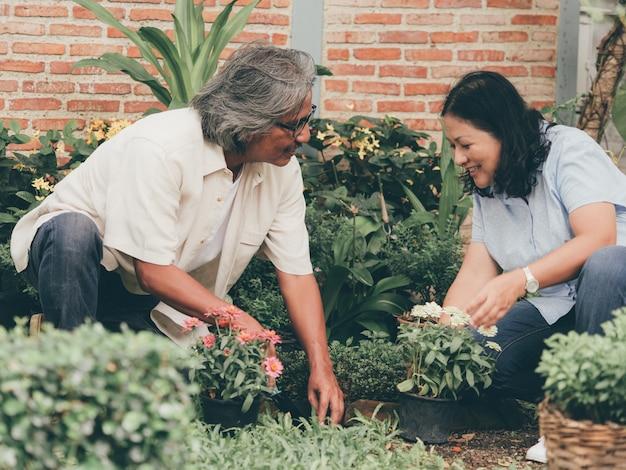 Portrait de couple senior dans le jardin de fleurs