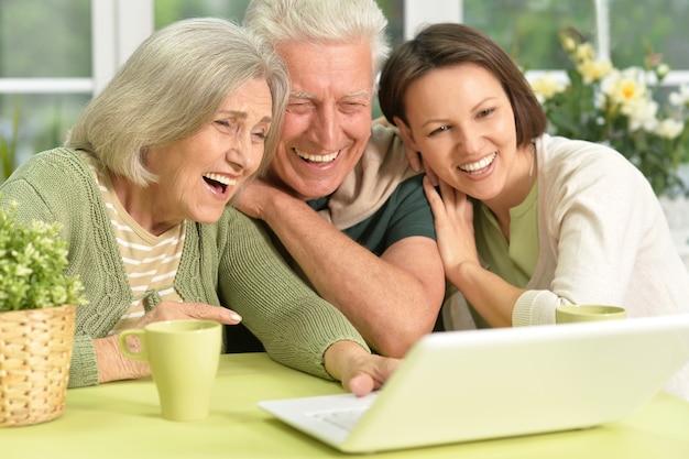 Portrait de couple senior avec ordinateur portable avec fille attentionnée