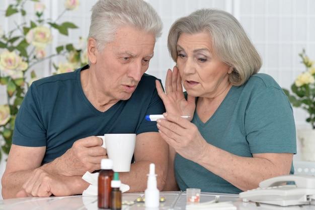Portrait de couple senior avec des pilules à la maison