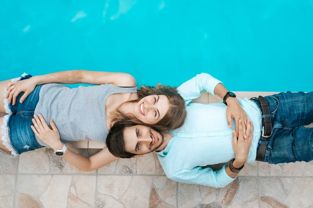 Portrait de couple souriant allongé habillé près de la piscine. ils s'aiment