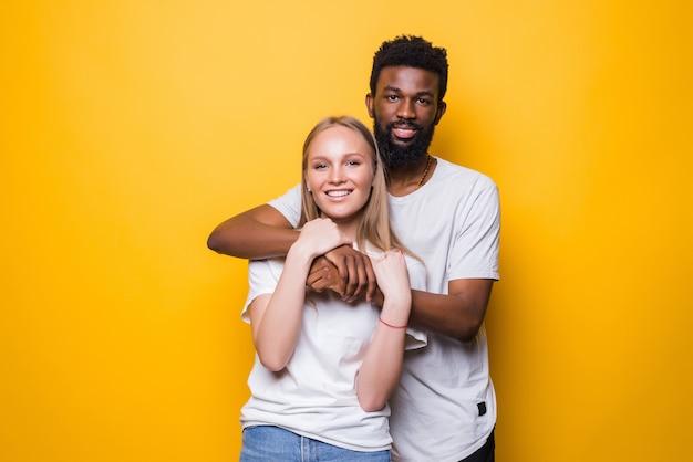 Portrait d'un couple souriant de race mixte posant sur un mur jaune en studio et regardant à l'avant