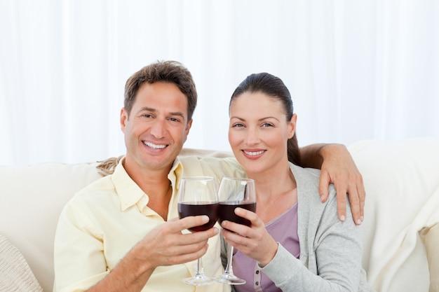 Portrait d'un couple tinter les verres de vin rouge sur le canapé