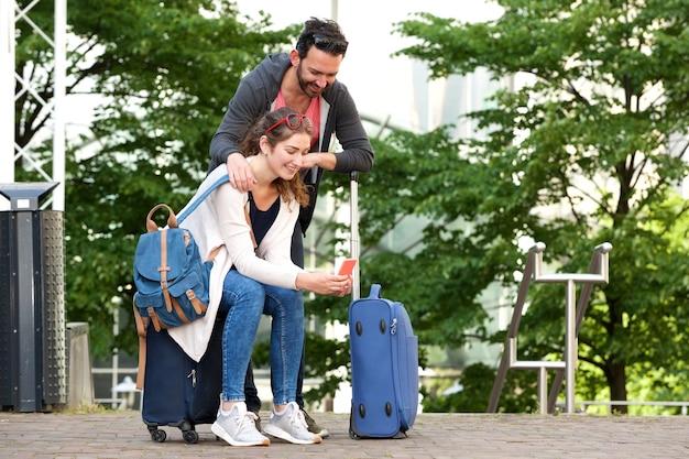 Portrait de couple de touristes heureux à l'extérieur avec des bagages dans la ville