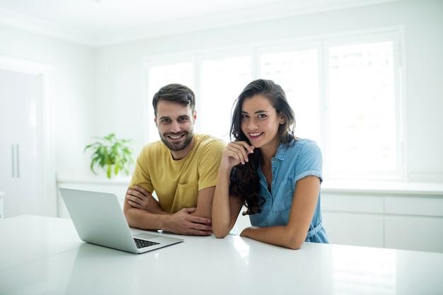 Portrait de couple utilisant un ordinateur portable dans la cuisine à la maison