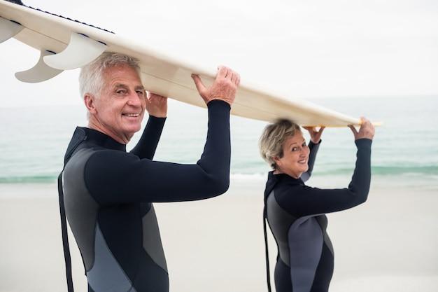 Portrait, de, couples aînés, dans, wetsuit, porter, planche surf, sur, tête