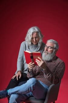 Portrait, couples aînés, lecture livre, contre, fond rouge