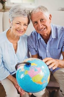 Portrait, de, couples aînés, tenir globe, et, sourire, dans, salle de séjour