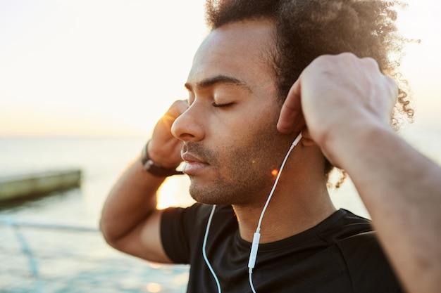 Portrait de coureur afro-américain médiateur et paisible avec une coiffure touffue et les yeux fermés écoutant de la musique. tourné en plein air d'un sportif à la peau sombre en t-shirt noir se détendre après l'entraînement du matin ses