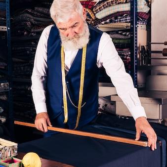 Portrait d'un créateur de mode masculin senior, mesurant le tissu avec une règle en bois