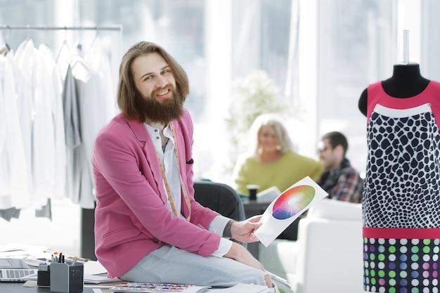 Portrait d'un créateur de vêtements assis sur un bureau