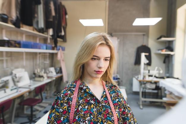 Portrait d'un créateur de vêtements au travail dans l'arrière-plan d'un studio.