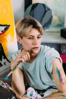 Portrait créatif de la belle jeune femme artiste en studio avec des pinceaux