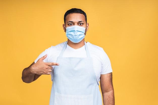 Portrait d'un cuisinier afro-américain noir et indien positif en tablier et masque de protection regardant la caméra isolée sur fond jaune. notion de coronavirus.