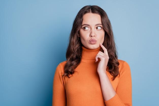 Portrait de curieuse fille rusée look espace vide moue lèvres doigt joue isolé sur fond bleu