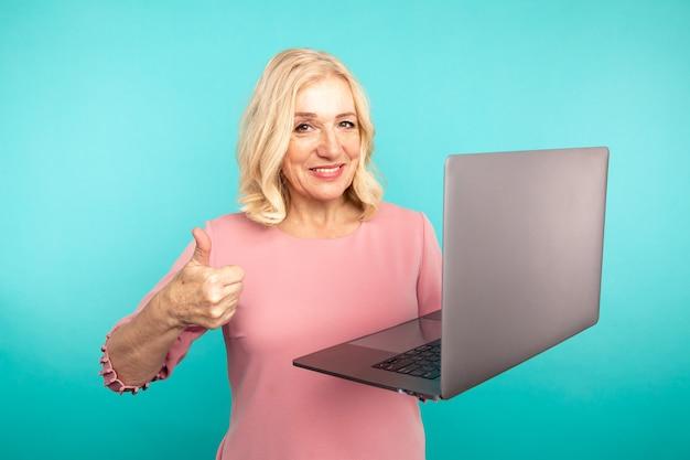 Portrait de dame abulte heureuse sortie avec ordinateur portable isolé sur le studio bleu.
