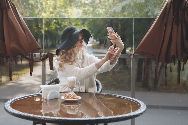 Portrait d'une dame blonde dans un chapeau noir à une table dans un café avec un smartphone, cheveux longs, un manteau beige. prendre un selfie.