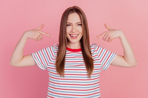 Portrait d'une dame charmante positive et folle qui dirige les doigts elle-même sur fond rose