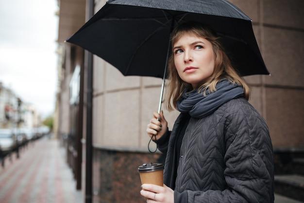 Portrait de dame debout sur rue avec parapluie noir et café dans les mains tout en regardant sérieusement de côté