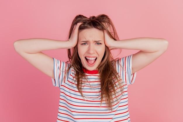 Portrait d'une dame furieuse en colère agressive hurlant d'humeur sur fond rose