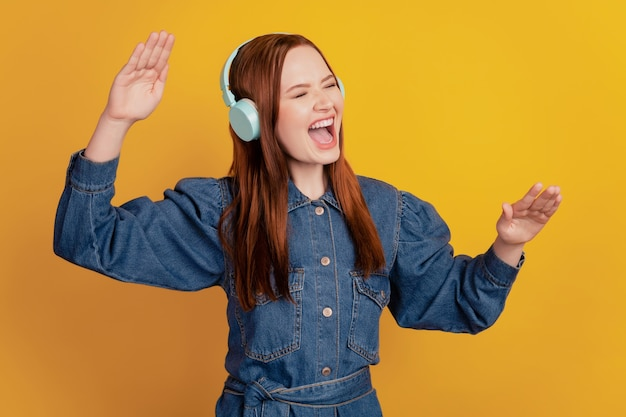 Portrait de dame insouciante porter des écouteurs sans fil écouter de la musique chanter sur fond jaune