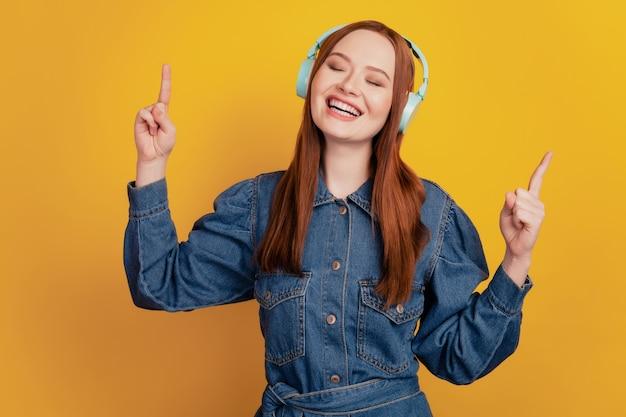 Portrait de dame inspirée rêveuse porter des écouteurs écouter de la musique lever les doigts sur fond jaune