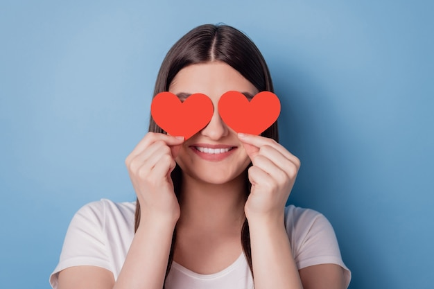 Portrait d'une dame mignonne adorable et drôle tenir une petite couverture de carte postale en forme de coeur rouge fermer les yeux sur fond bleu