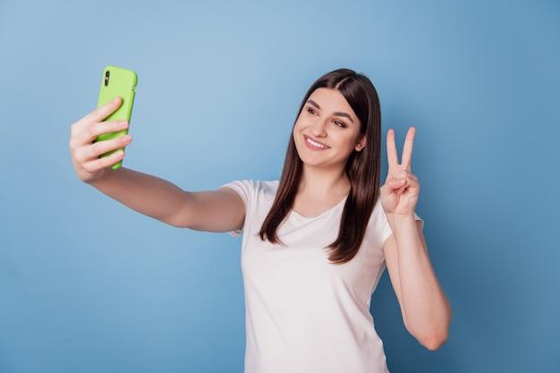 Portrait d'une dame positive et amicale tenir le téléphone faire un selfie show v-sign sur fond bleu