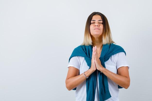 Portrait de dame avec pull attaché montrant les mains jointes dans un geste de plaidoirie en t-shirt blanc et à la vue de face pleine d'espoir