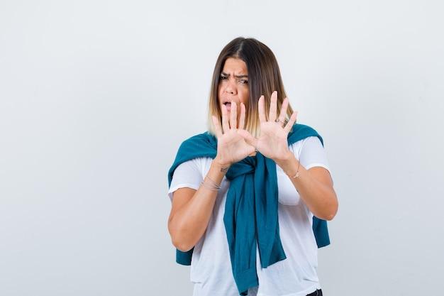 Portrait de dame avec pull noué montrant un geste d'arrêt en t-shirt blanc et à la vue de face effrayée