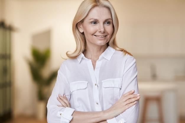 Portrait de dame réussie d'une femme mûre élégante portant une chemise blanche souriante de côté tout en posant