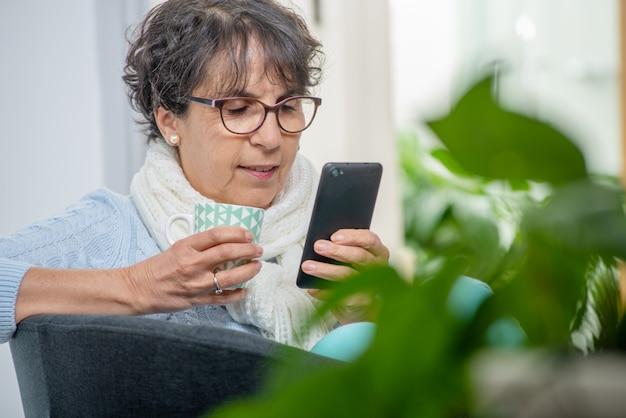 Portrait de dame senior à l'aide d'une application sur son smartphone