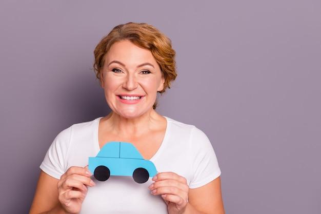 Portrait de dame en t-shirt blanc tenant une voiture en papier isolée sur violet