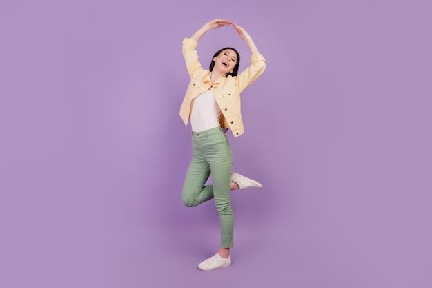 Portrait d'une danse insouciante d'inspiration fille lever les mains sur fond violet