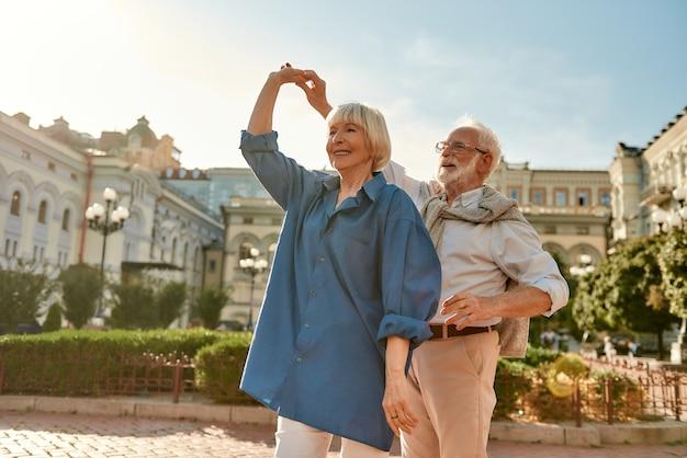 Portrait de danse spontanée d'un couple de personnes âgées heureux souriant tout en dansant ensemble à l'extérieur