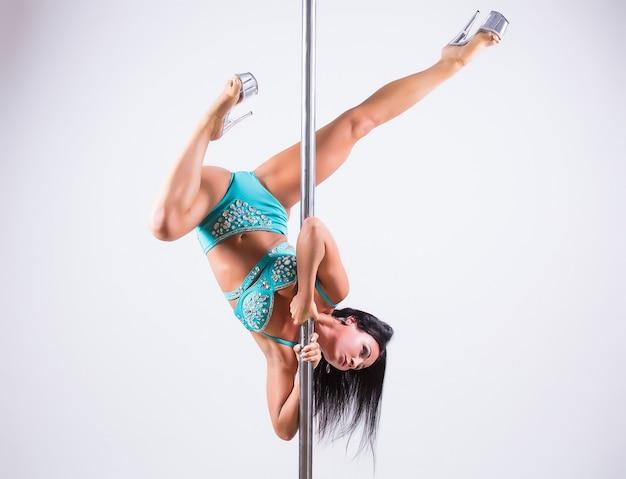 Portrait d'une danseuse flexible en équilibre sur poteau. isolé sur fond blanc