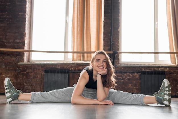 Portrait d'une danseuse souriante assise sur le sol avec ses jambes tendues